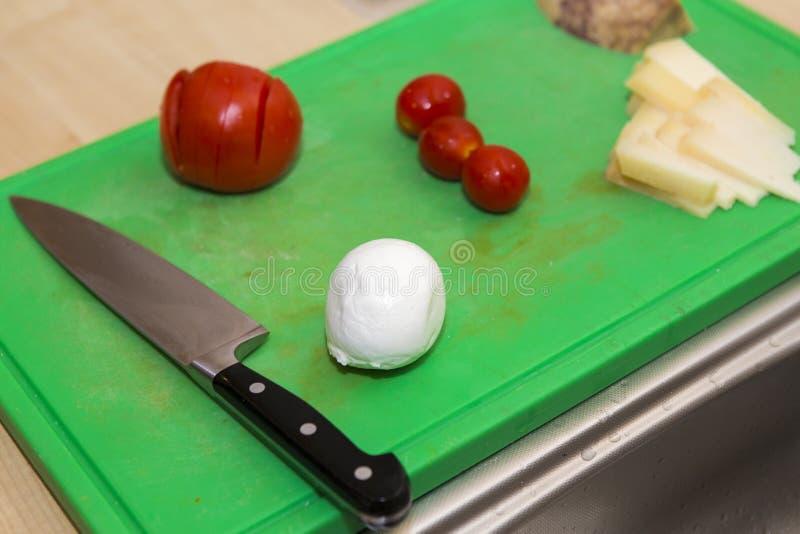 Mussarela do corte, tomates, makin do queijo uma pizza imagem de stock royalty free