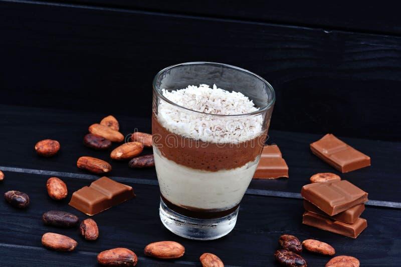 Musse do chocolate em um frasco de vidro na tabela preta foto de stock