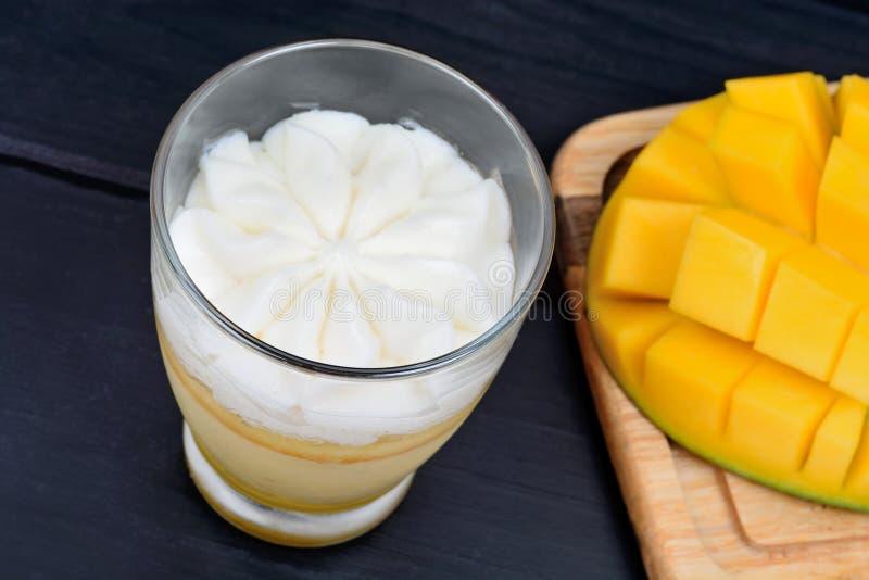 Musse do fruto da manga com chantiliy em um frasco de vidro e em cubos da manga em uma tabela fotos de stock