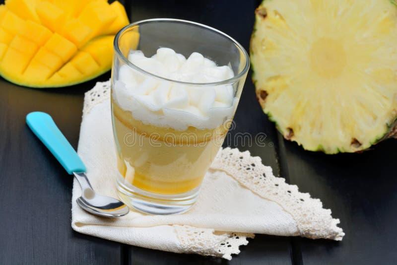 Musse do fruto e do abacaxi da manga em um frasco de vidro na tabela preta imagens de stock