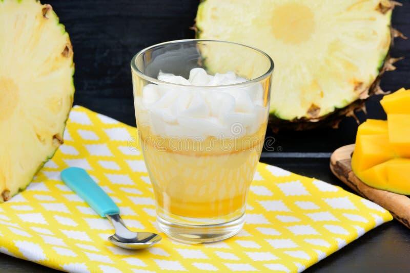 Musse do fruto e da manga do abacaxi em um frasco de vidro na tabela imagens de stock