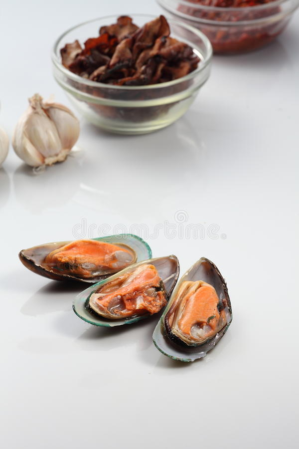 Mussel. Three pieces of mussel with ingredient as background royalty free stock images