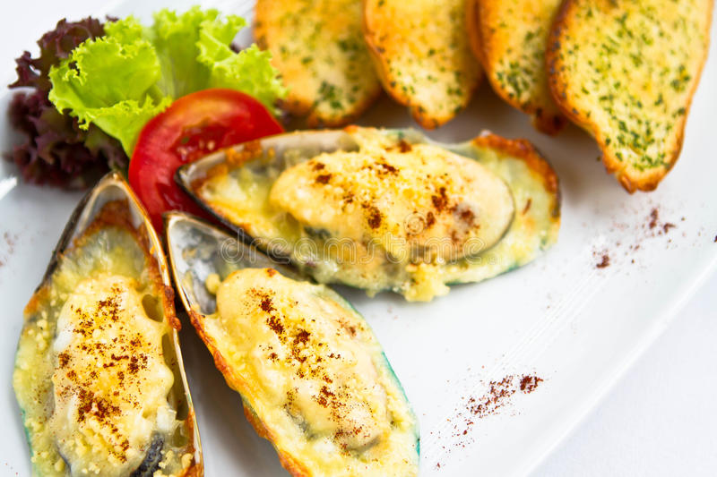 Mussel. Baked s with cheese and garlic bread royalty free stock images