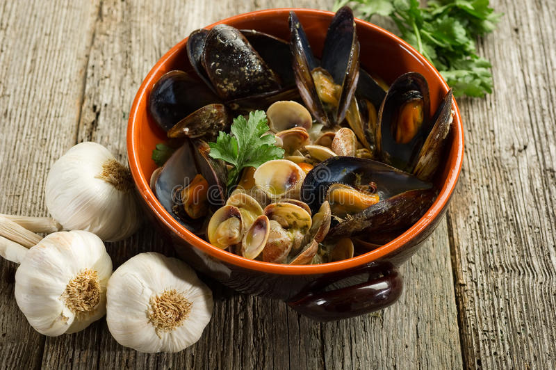 Mussel and soup. On bowl over wood background royalty free stock images
