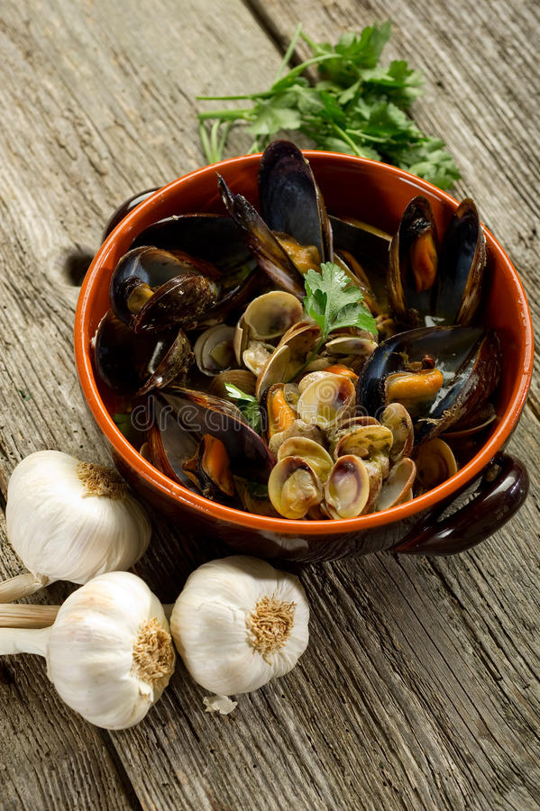 Mussel and soup. On bowl over wood background stock photos
