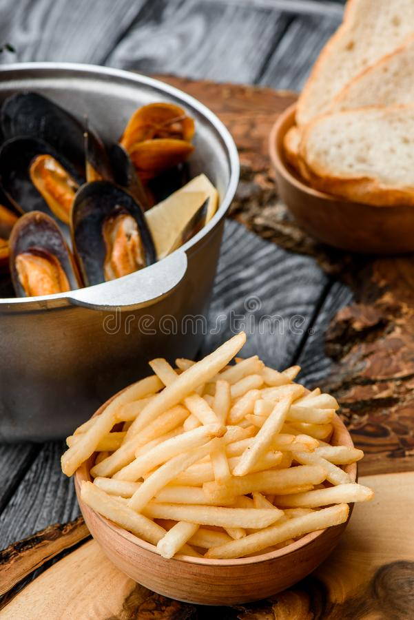 Mussel shells in a gray cauldron in tomato sauce, french fries and croutons on a gray background royalty free stock images
