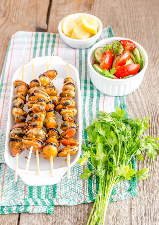 Mussel skewers with fresh salad stock image