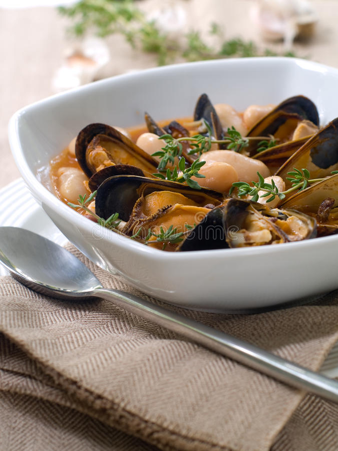 Mussel soup. With bean and thyme on bowl royalty free stock images
