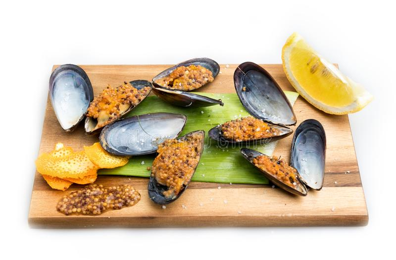 Mussels baked with mustard and orange peel stock image