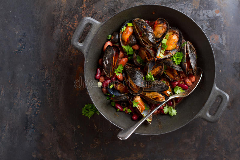 Mussels in cast iron pot. With bean and herbs, selective focus royalty free stock images