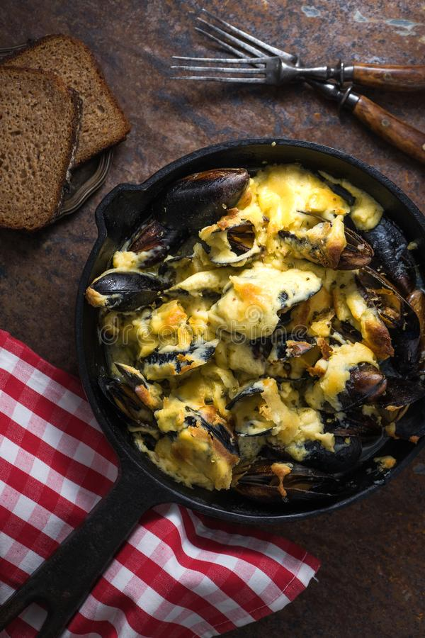 Mussels with cheese sauce in a frying pan, napkin in a red cage royalty free stock photography