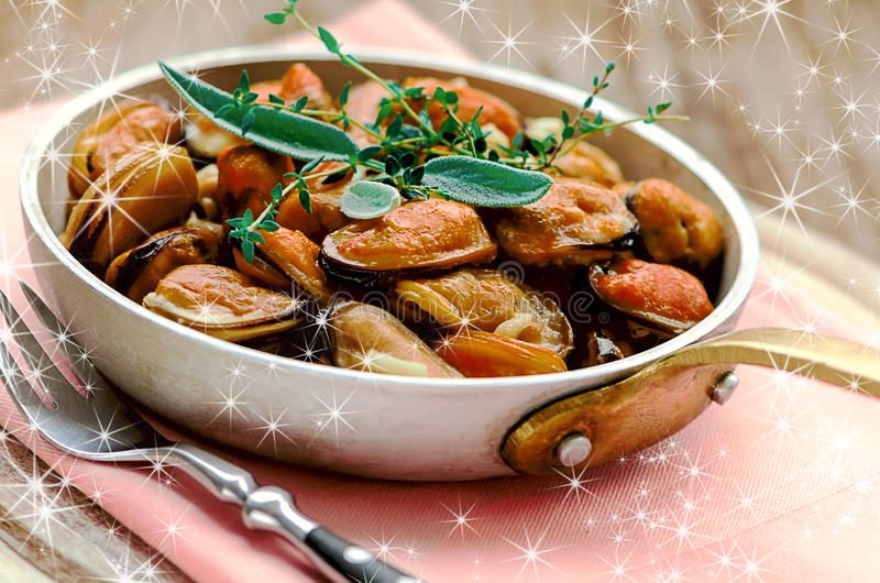 Mussels in cream and garlic sauce with provencal herbs. In the pan royalty free stock image