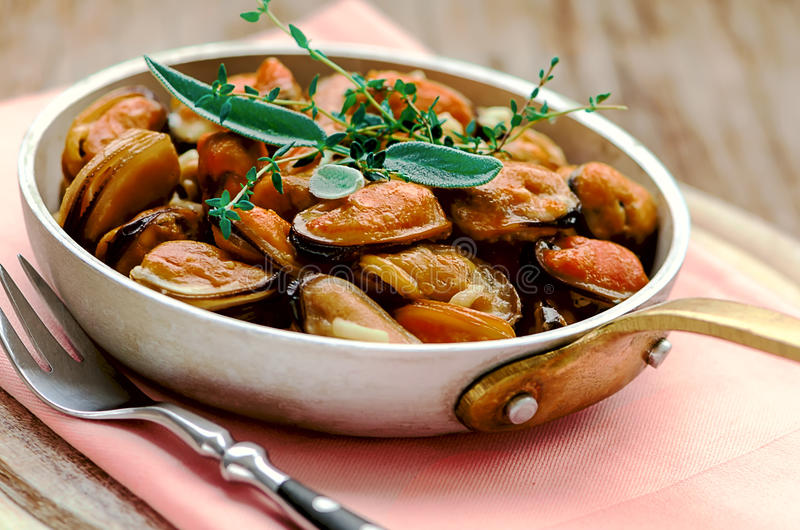 Mussels in cream and garlic sauce with provencal herbs. In the pan stock image
