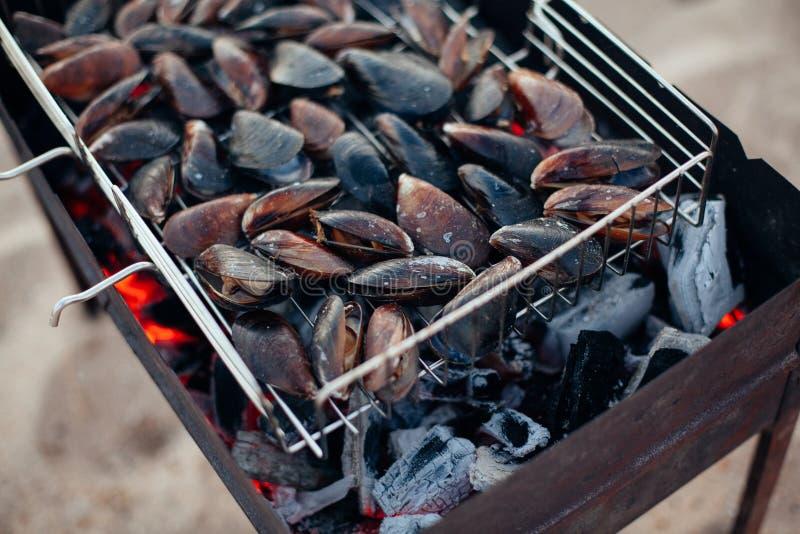Mussels na grillu Owoce morza grill outdoors na piasek plaży Jedzenie i wakacje zdjęcie royalty free