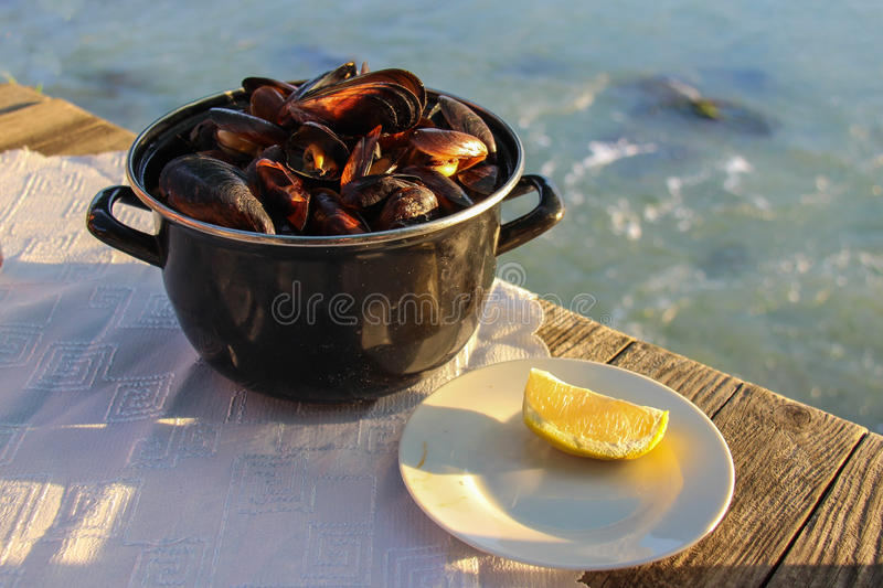 Mussels at Dalboka Seafood Restaurant. A tinpot full of boiled mussels and a slice of lemon. Seafood specialty at Dalboka Seafood Restaurant in Kavarna Bulgaria royalty free stock photos