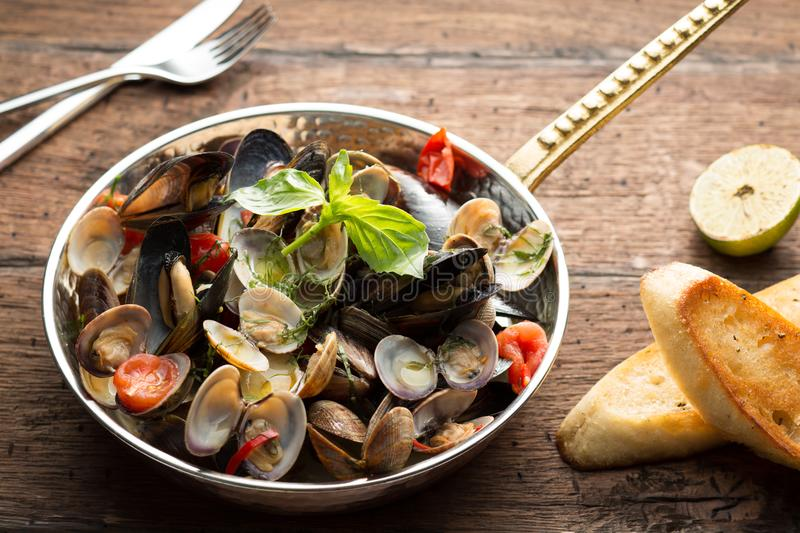 Mussels and shellfish served with bread and lime in a frying pan on the wooden vintage background stock photos