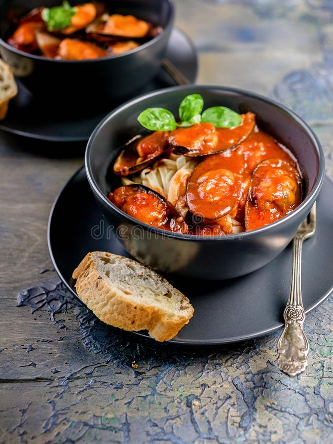 Mussels in tomato sauce with spaghetti in a dark plate. Mussels pasta. Mediterranean Kitchen. Vertical shot stock photo