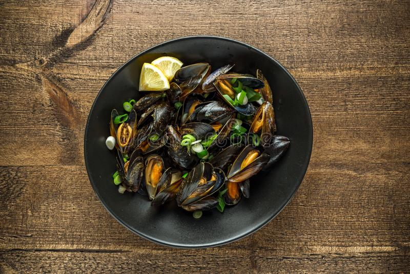 Mussels w czosnku masła kumberlandzie słuzyć z cytryną na drewnianym stole zdjęcie stock