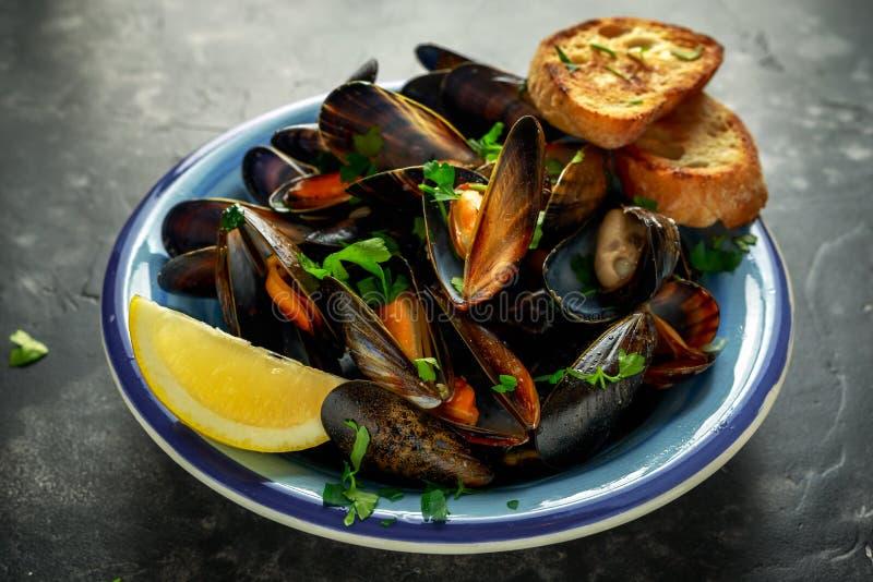 Mussels w czosnku masła kumberlandzie słuzyć z pietruszką, grzanką i cytryną, obraz royalty free