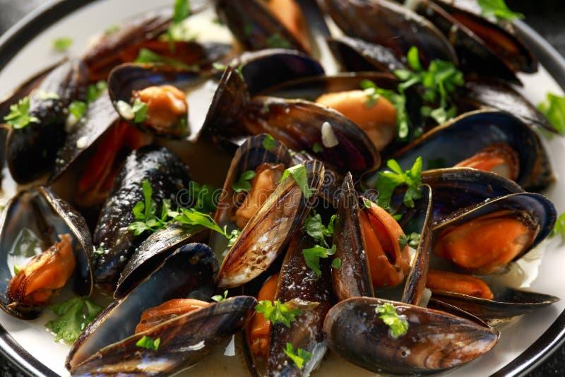 Mussels z bia?ym winem, czosnkiem, cytryn? i ziele w talerzu, francuz sma?? Rustick t?o Owoce morza obraz royalty free