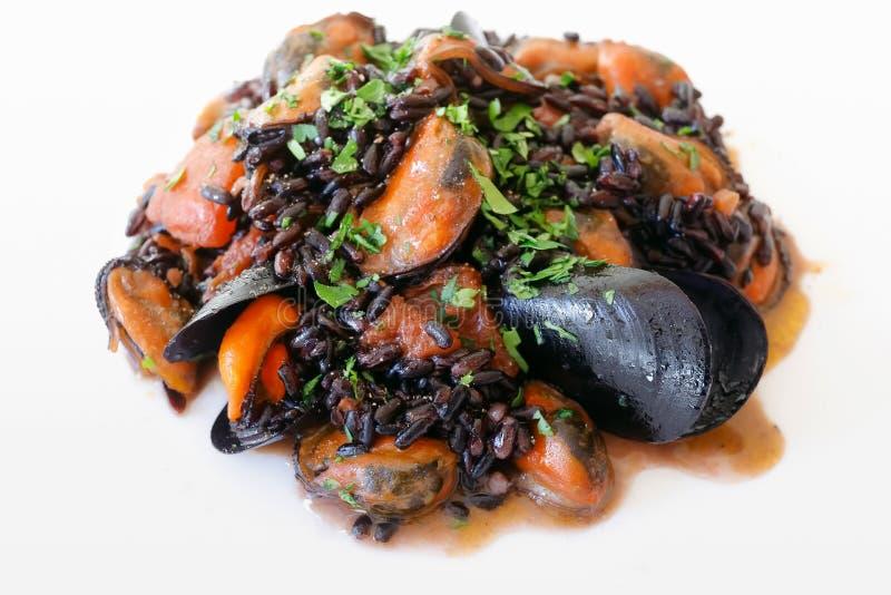 Mussels z ryż, pomidorem, olejem, czosnkiem i basilem czarnymi, przygotowywający jeść obraz stock