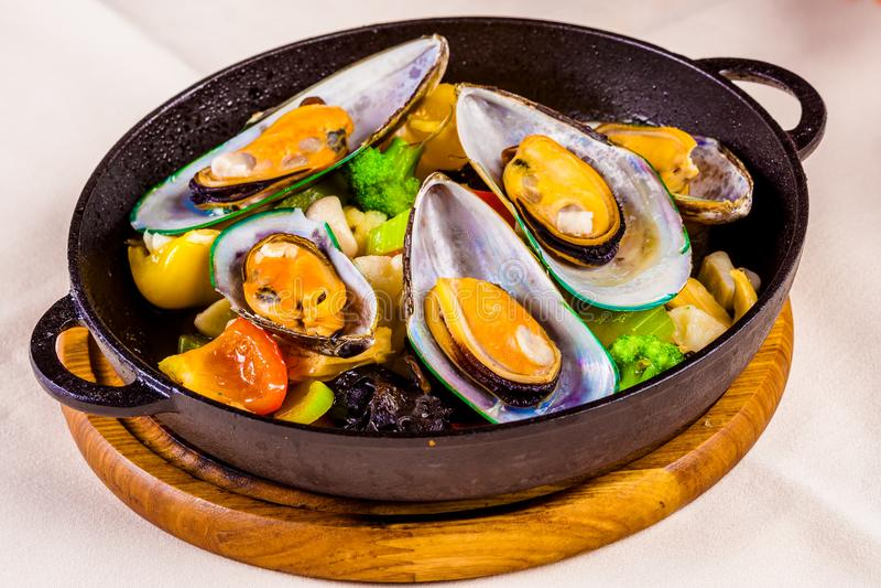 Mussels z warzywami w czarnym garnku obrazy royalty free