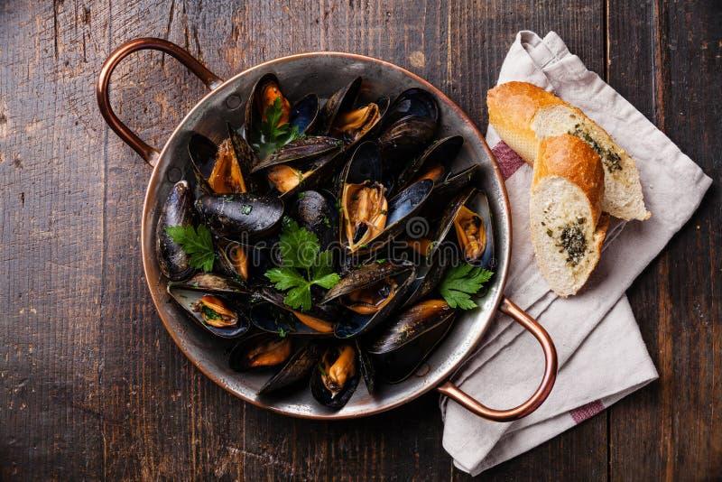 Musslor och fransk bagett med örter arkivfoto