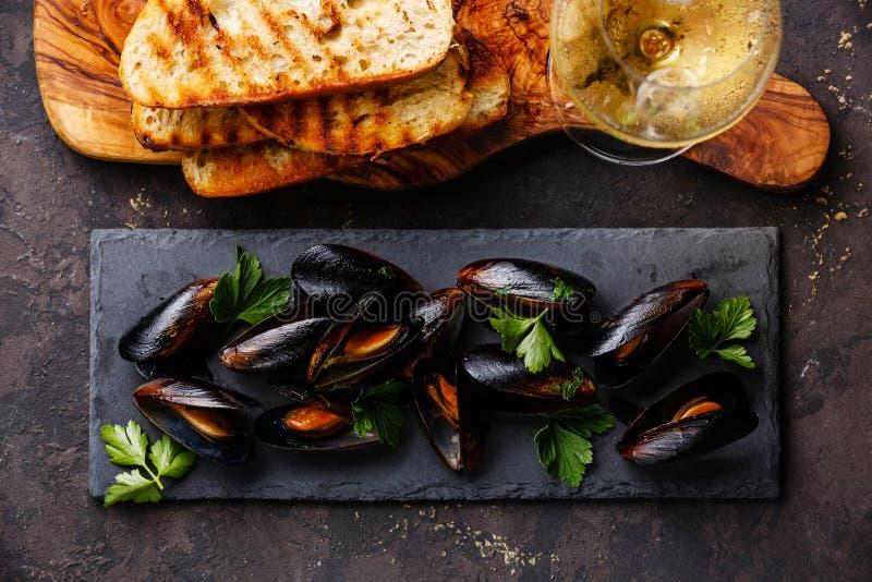 Musslor, rostade bröd och vin royaltyfria bilder