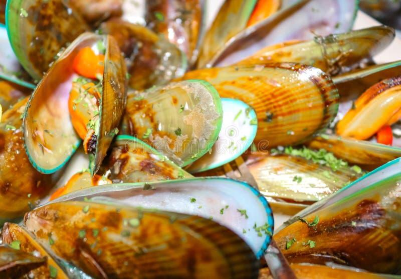 Musslor som lagas mat i läckra och klart smör och örter att äta - defocused och bokeh fotografering för bildbyråer