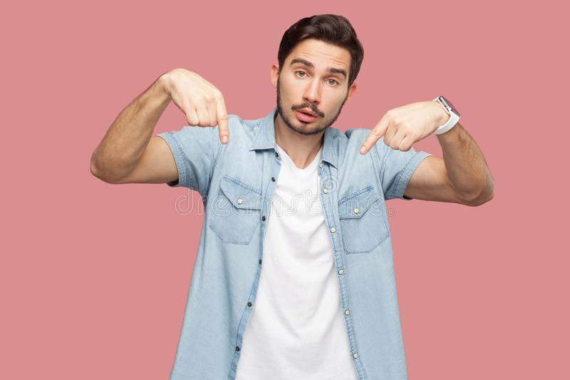 Must be here and right now. Portrait of serious handsome bearded young man in blue casual style shirt standing, pointing down and stock photography