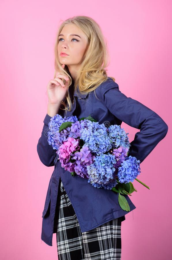Must have concept. Clothes and accessory. Woman blonde hair posing coat with flowers bouquet. Fashionable coat. Girl. Fashion model wear coat for spring and stock photos