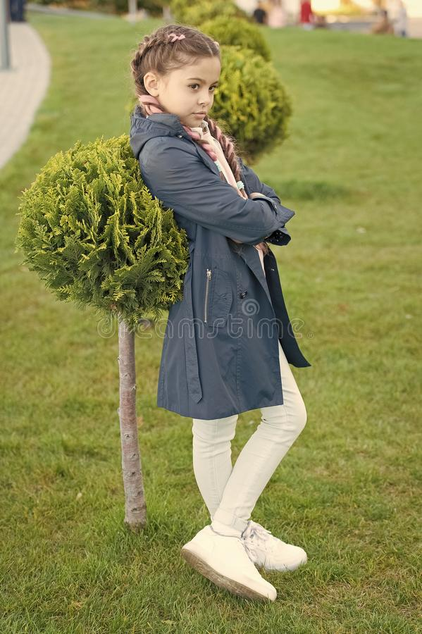 Must have concept. Fashionable coat. Girl cute face braided hair posing coat in spring park. Clothing for spring walks. Little fashion model. Clothes and stock image