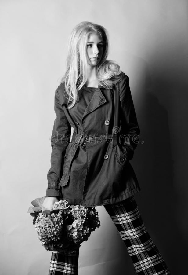 Must have concept. Fashionable coat. Woman blonde hair posing coat with flowers bouquet. Clothes and accessory. Girl. Fashion model wear coat for spring and royalty free stock image