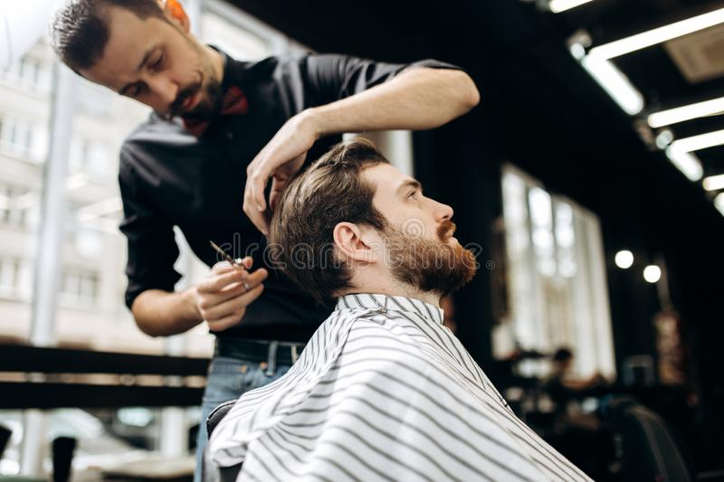 Mustachioed barber dressed in a black shirt with a red bow tie makes a stylish hairstyle to young man in a barbershop stock image