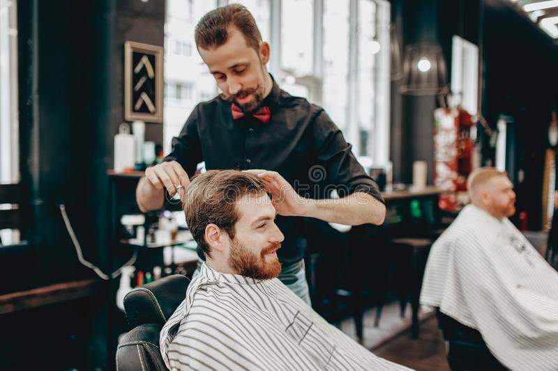 Mustachioed barber dressed in a black shirt with a red bow tie makes a stylish hairstyle to young man in a barbershop royalty free stock image