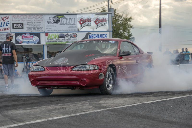Mustang smoke show. Front side view of red ford mustang making a smoke show on the track during the john scotti all out 17-19 june 2016 stock photo