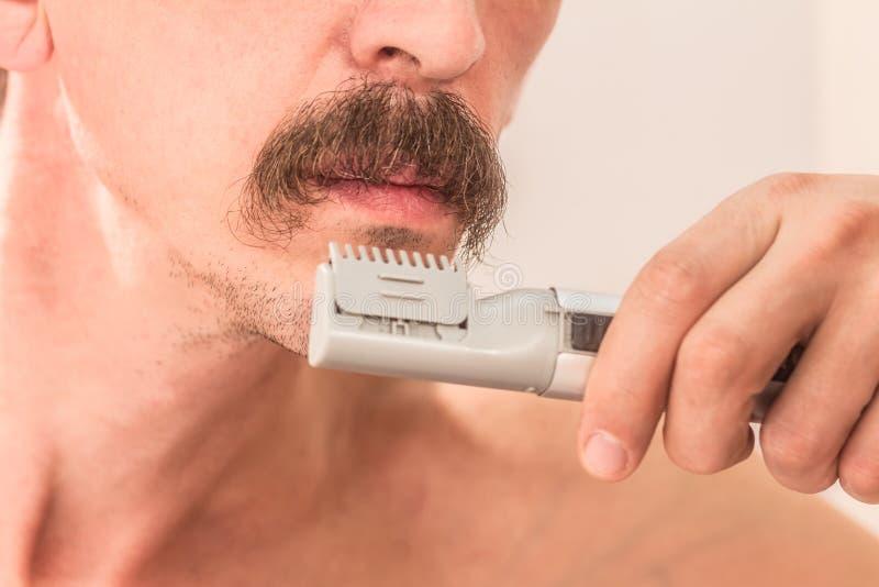 Mustasch och hand för man` som s rakar beskäraren Närbild royaltyfria bilder