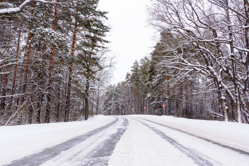Muster auf der Winterlandstraße in Form von vier Geraden Snowy-Straße auf dem Hintergrund des schneebedeckten Waldes stockbild