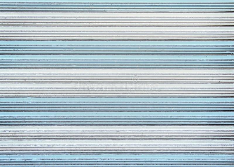 Muster der bunten alten weißen und blauen rollenden Stahltürbeschaffenheit oder der Rollenfensterladentür für Hintergrund lizenzfreie stockbilder