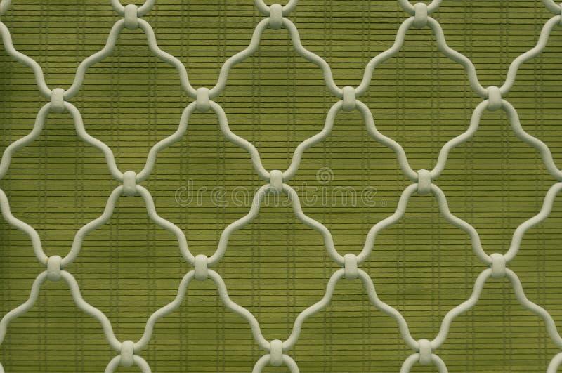 Muster der Diamantform auf weißem gebogenem Schmiedeeisenstahl auf dem Gitterfenster, grüner Bambusvorhanghintergrund, Weinlesear lizenzfreie stockfotos