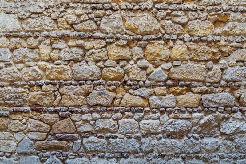 Muster des gelben und grauen dekorativen Schmutzes verwitterte ungleiche Steinwandoberfläche lizenzfreies stockfoto