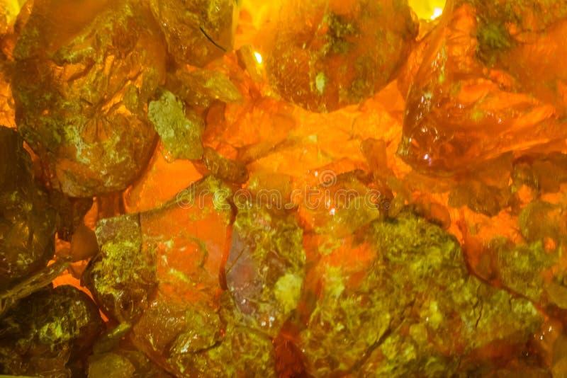 Muster des orange glühenden Mineralsteins in der Makronahaufnahme, Bergbauhintergrund lizenzfreies stockbild