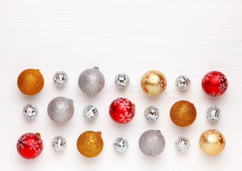 Muster von bunten Bällen der Weihnachtsspielwaren auf weißem hölzernem Hintergrund lizenzfreie stockbilder