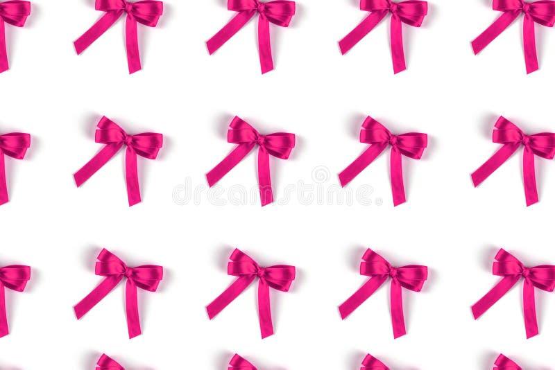 Muster von den rosa Seidengeschenkb?gen lokalisiert auf Wei? lizenzfreies stockbild