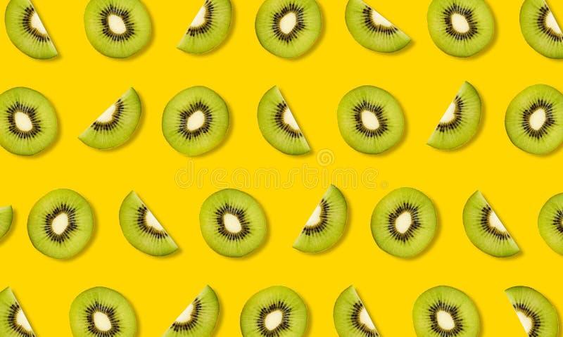Muster von den Scheiben der Kiwi auf gelbem Hintergrund lizenzfreie stockbilder