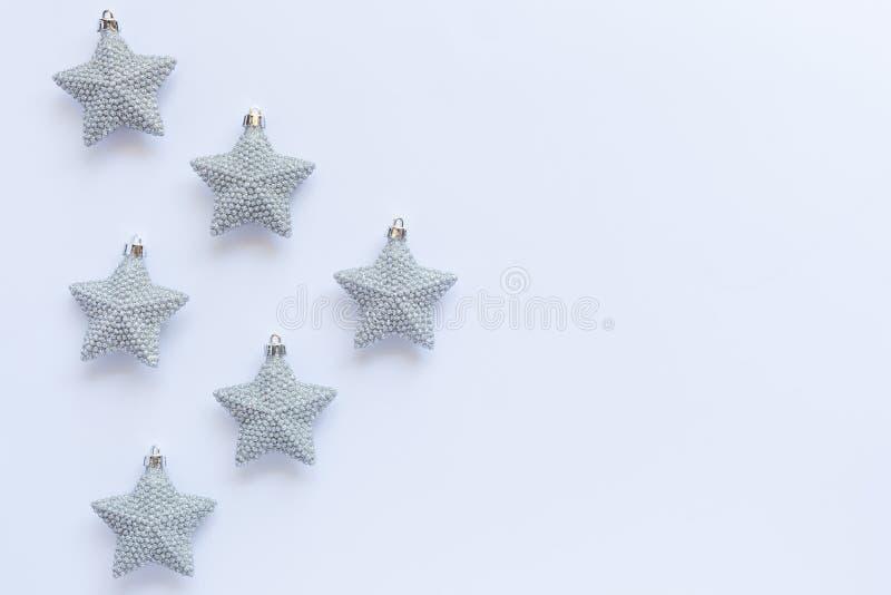 Muster von silbernen glittery Weihnachtssternverzierungen auf weißem BAC lizenzfreies stockbild