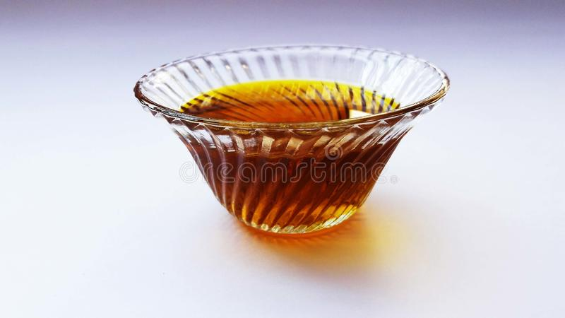 Mustered oil in bowl isolated on white background. Yellow, cooking, olive, food, ripe, sun, fruit, planks, wood, italian, tree, field, maturation, green, fresh royalty free stock images