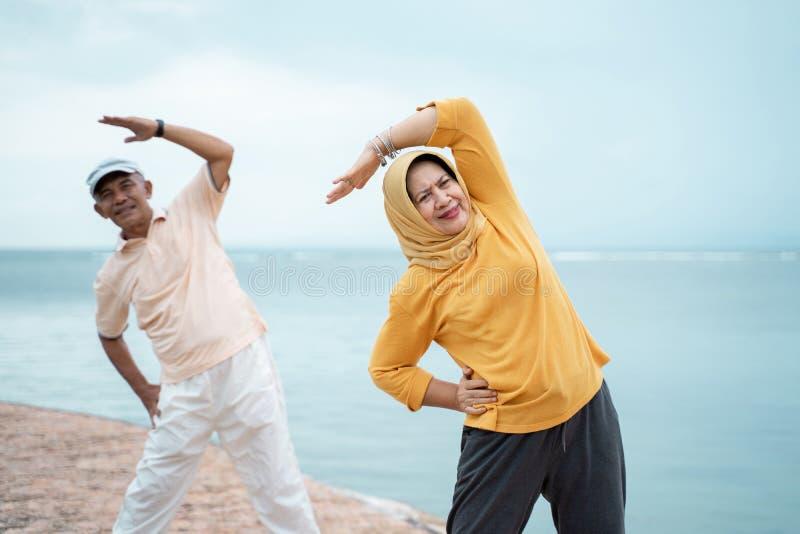 Musulmanes asiáticos de los pares que estiran y que ejercitan junto imagen de archivo