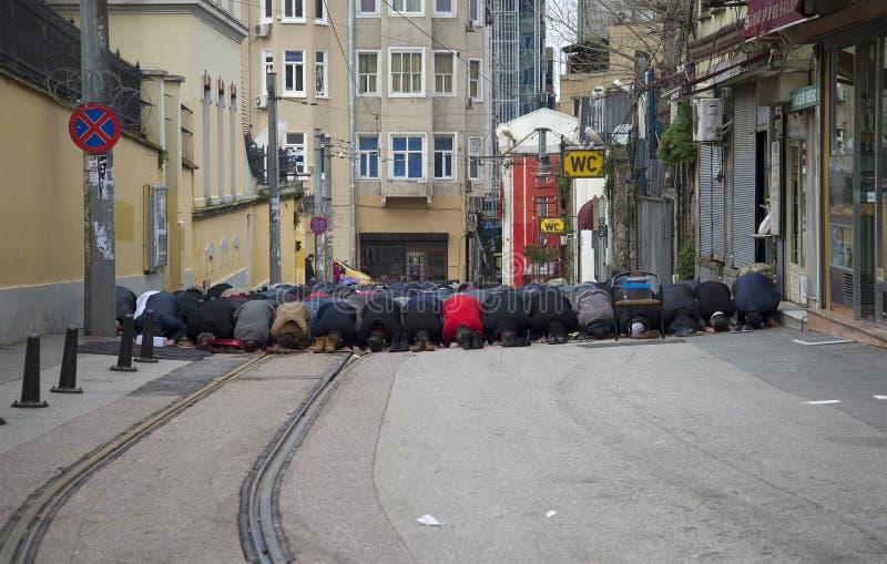 Musulmanes masculinos que ruegan en la calle Estambul, Turquía fotografía de archivo
