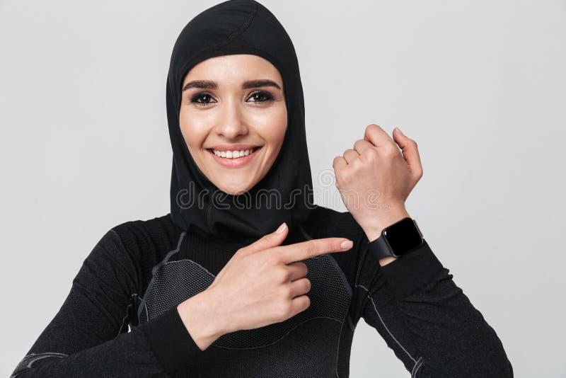 Musulmani di forma fisica della giovane donna che per mezzo dell'orologio dell'orologio isolato sopra il fondo bianco della paret fotografia stock libera da diritti